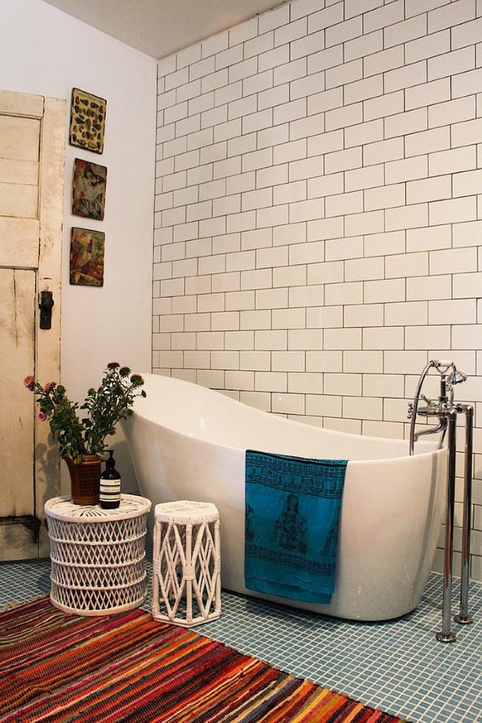 bathroom decorating ideas on a budget, white subway tiles on the wall of a room, containing a white modern bathtub, pale blue mosaic floor, and a multicolored striped rug, flowers and white rattan furniture