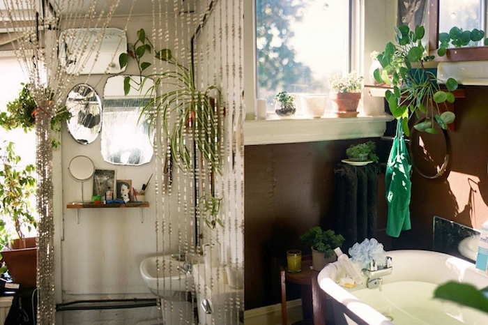 small bathroom décor, two examples of boho bathrooms, one with several mirrors on the wall, a beaded curtain, and lots of potted plants, and one with brown walls, and a white bathtub