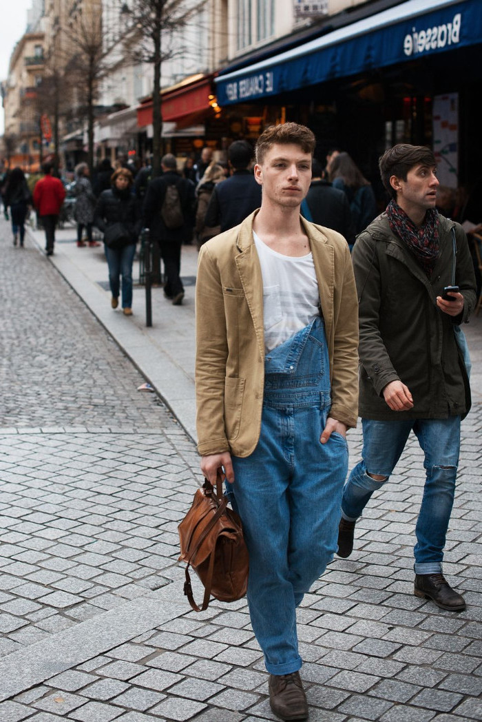 blazer in beige, with long baggy, half unbuttoned denim overalls, worn by a young man, holding a brown leather bag