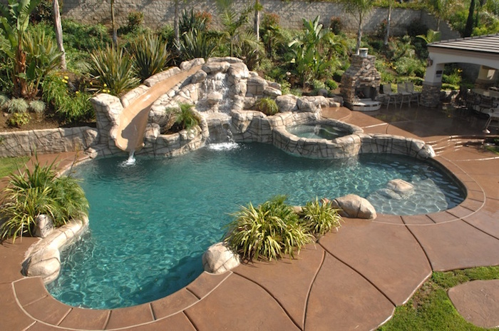 decorations made of stone, around a small pool, surrounded by beige stone tiles, cool backyards, spout-like construction, pouring water into the pool