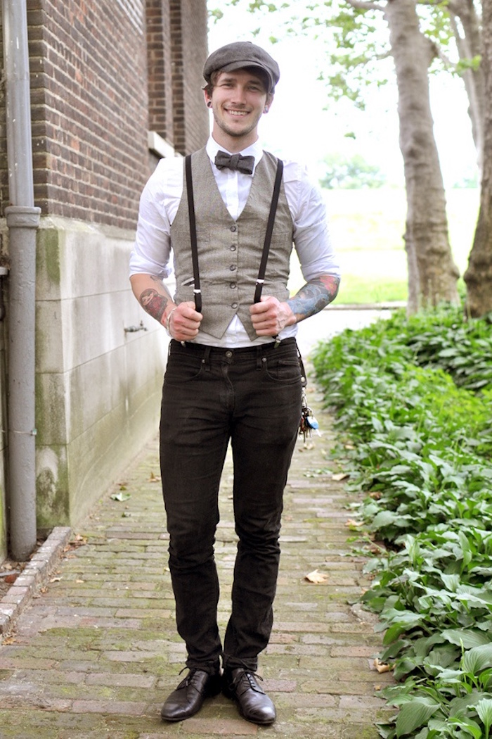 trousers in black, worn with suspenders, a white shirt and a beige vest, and a brown bowtie, 20s mens fashion, on a smiling man with a cap, and forearm tattoos