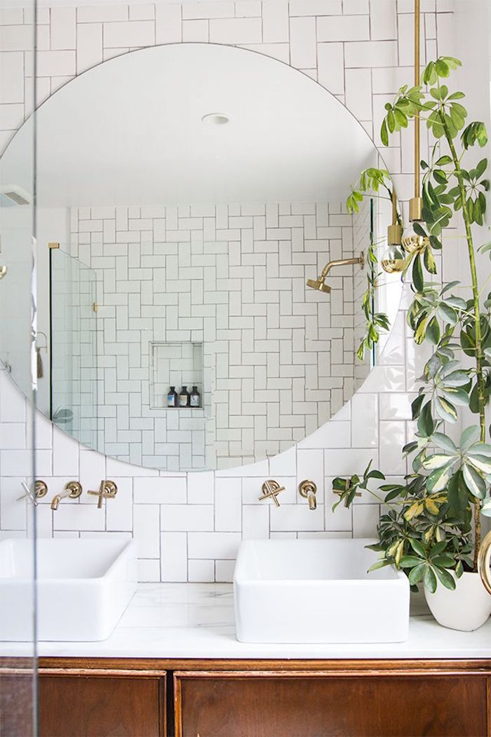 herringbone subway tiles in white, and a large round mirror, in a room with two sinks, and a potted plant, bathroom decorating ideas on a budget, retro wooden cupboard