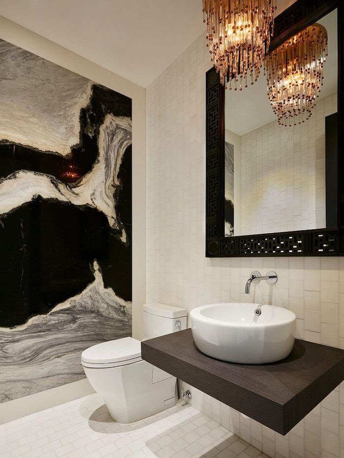 stone-effect wall in black, white and grey, inside a bathroom with white subway tiles, on the floor and other visible wall, large mirror in black frame, toilet and sink