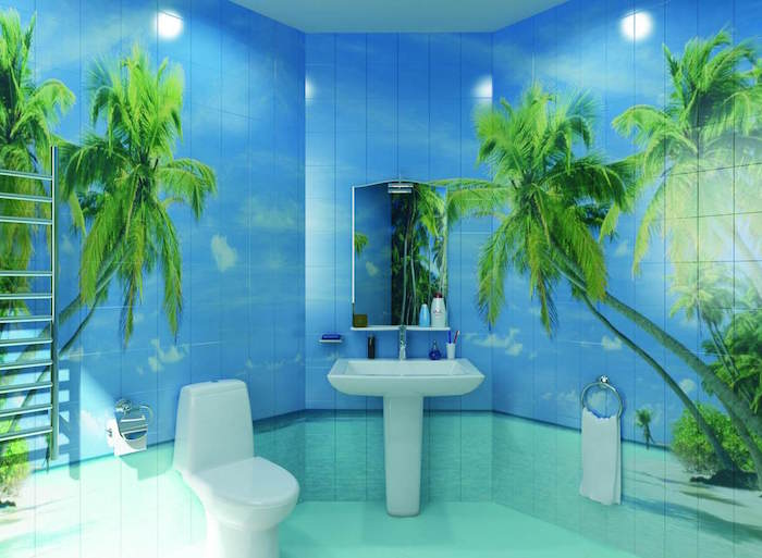 tiles in pale blue and turquoise, with images of a beach, with green palm trees, on the walls of a bathroom, containing a white ceramic toilet seat, and a matching sink
