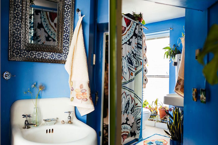 azure blue walls, and a vintage white sink, with rounded edges, in a room with a small mirror, in a detailed ornamental frame, small bathroom decoration ideas, multicolored shower curtain, and potted plants