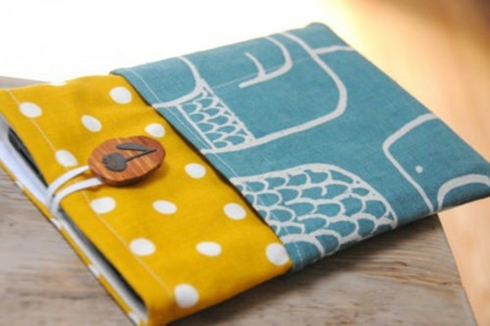 fabric book cover, in mustard yellow, and teal blue, decorated with white polka dots, and off-white patterns, and a wooden button, cute gift ideas