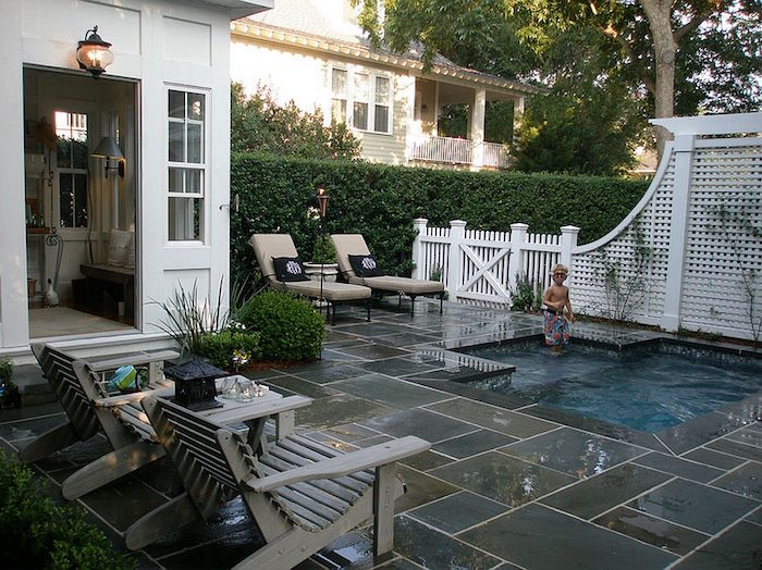 house with an open door, near a yard, covered in grey and beige stone tiles, containing a pool, with a child playing, cool backyards, two wooden chairs, and two sun beds