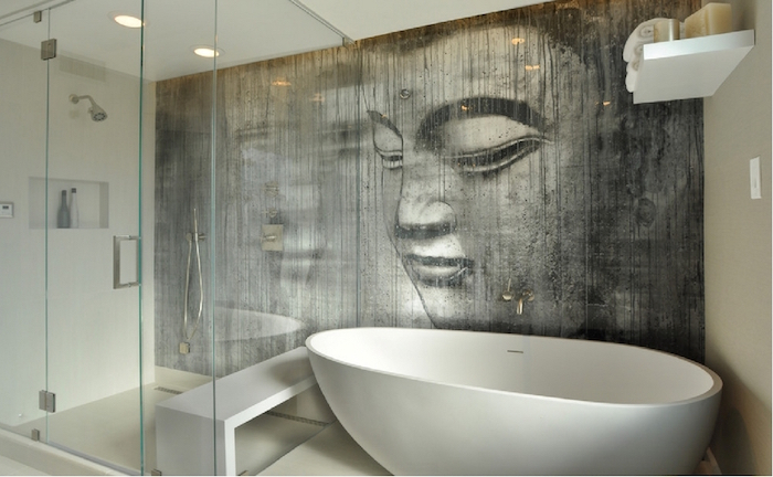 grey wall mural, depicting the face of Buddha, in a room with a glass shower cabin, and an oval white bathtub, bathroom wall decor ideas, of-white walls, and ceiling lights