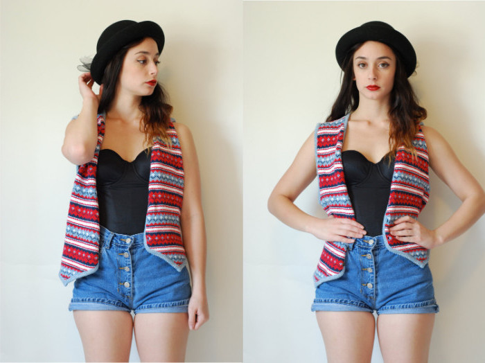 vest with a colorful pattern, worn over a black bustier, tucked into high waisted, button up denim shorts, on a young brunette girl, with a black hat