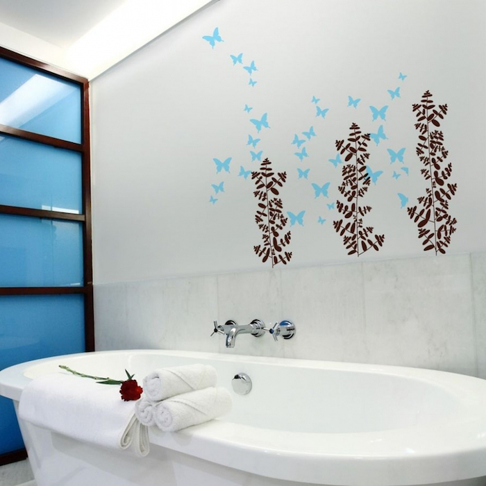 towels in white and a red rose, placed on a white oval bathtub, bathroom decorating ideas on a budget, nearby wall is decorated with blue and brown decal stickers, shaped like butterflies and plants
