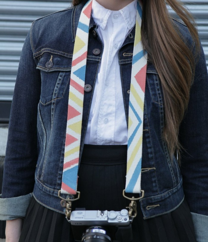 brunette woman in a black skirt, white shirt and a denim jacket, wearing a vintage camera, with a multicolored diy strap around her neck, inexpensive thank you gift ideas, geometrical figures in orange, yellow and blue