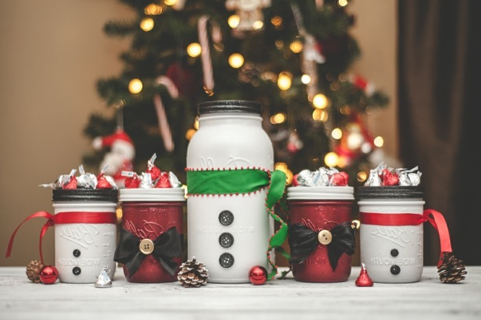 bows and buttons in black, and ribbons in red and green, decorating four small, and one large jars, painted in white and red, and filled with candy, creative gift ideas, christmas tree in the background