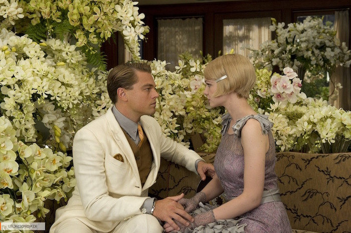 still from baz luhrmann's the great gatsby, featuring leonardo di caprio and carey mulligan, in great gatsby costumes, surrounded by white flowers