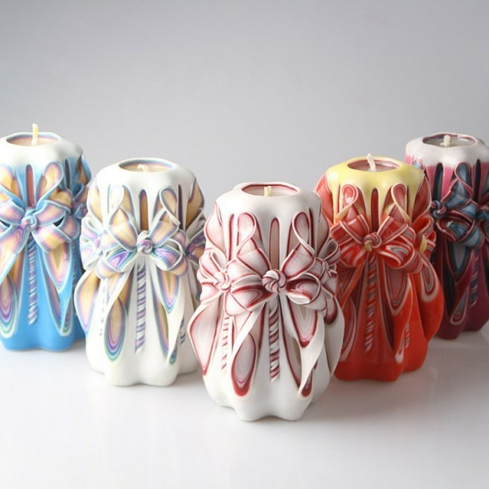 five large carved candles, in different colors, featuring bow-like details, on an off-white surface, cute birthday ideas