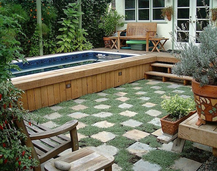 wooden stool near a bench, in a garden with lots of flowers and shrubs, containing a rectangular pool, lined with beige planks
