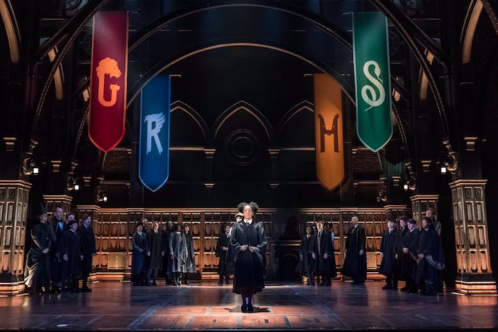 best set designers, children wearing black robes, standing on a stage, decorated with gothic elements, and colorful banners