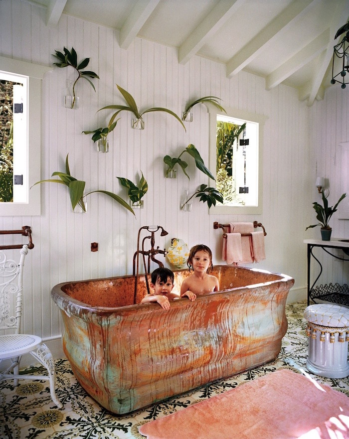 clear glass vases, mounted on a wall, covered in white wooden panelling, each containing different green leaves, diy bathroom décor, large vintage metal bathtub, with two small children