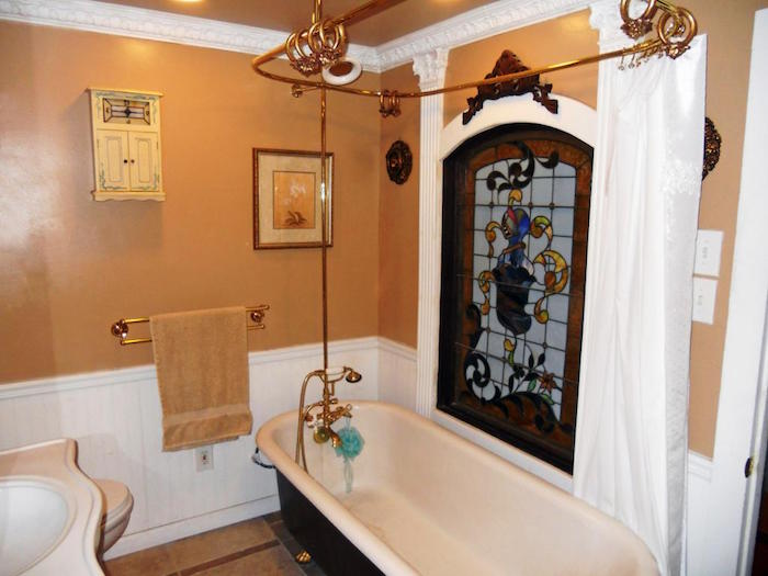 retro style bathroom, with beige walls, and white panelling, black and white oval bath, and a stained glass window, small bathroom décor, plaster details and a framed image