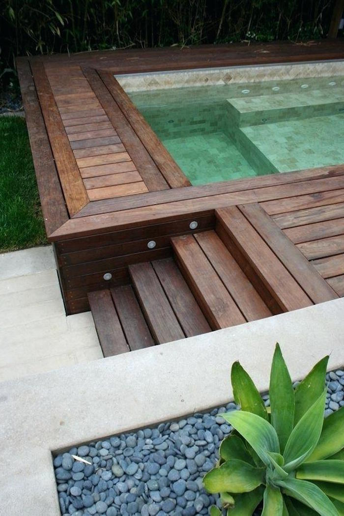 four wooden steps, leading up to a pool, surrounded by a wooden surface, pool patio ideas, flower bed with pebbles, and a green plant nearby