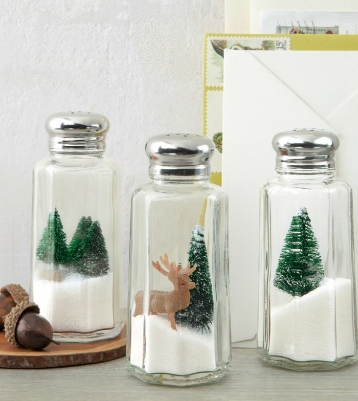 salt and pepper shakers, filled with faux snow, and decorated with tiny christmas trees, and a reindeer figurine, handmade gifts