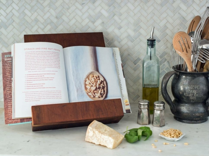 stand for cooking books, made of wood, holding an opened book, piece of cheese, basil leaves and nuts, condiments and utensils nearby