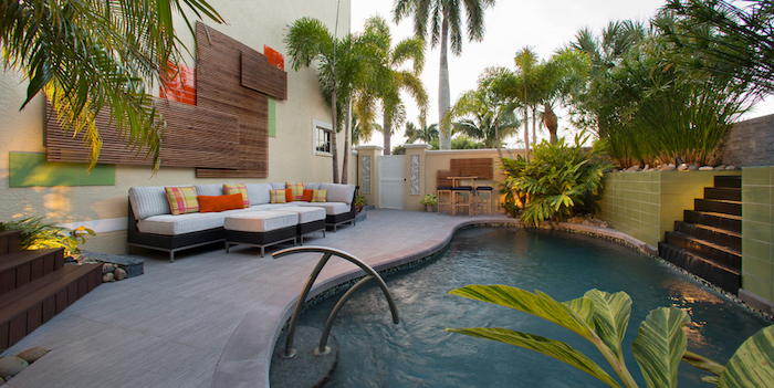 backyards with pools, black and white sofa, with two matching tables, and colorful yellow and orange cushions, in a garden with palms, other plants and a pool