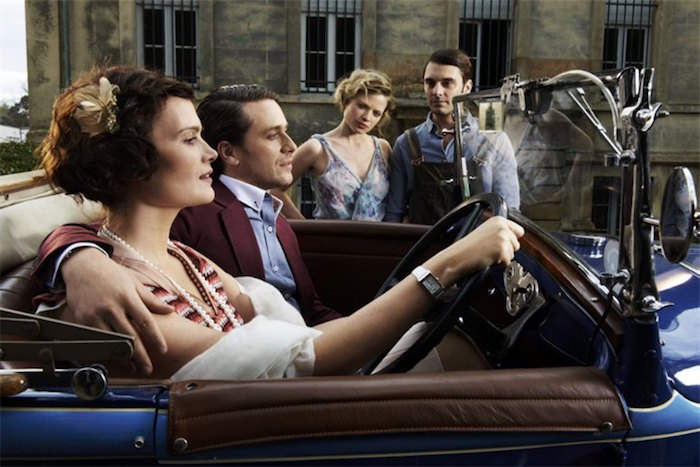 convertible blue antique car, with brown leather interior, driven by a young woman with bobbed hair, hugged by a man in a mauve blazer, roaring 20s fashion, another couple in the background