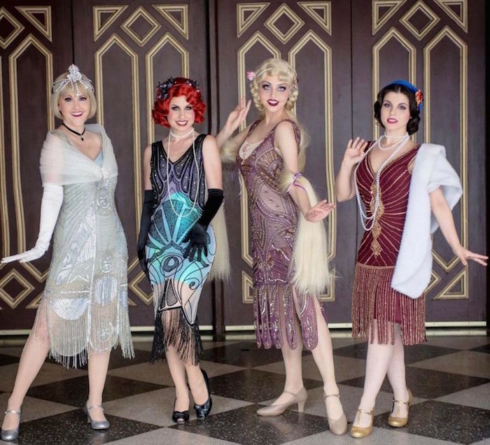 group of women, each in a different gatsby themed dress, pale blue and silver, turquoise and black, pink and purple, red and gold, all with embroidery and fringe details