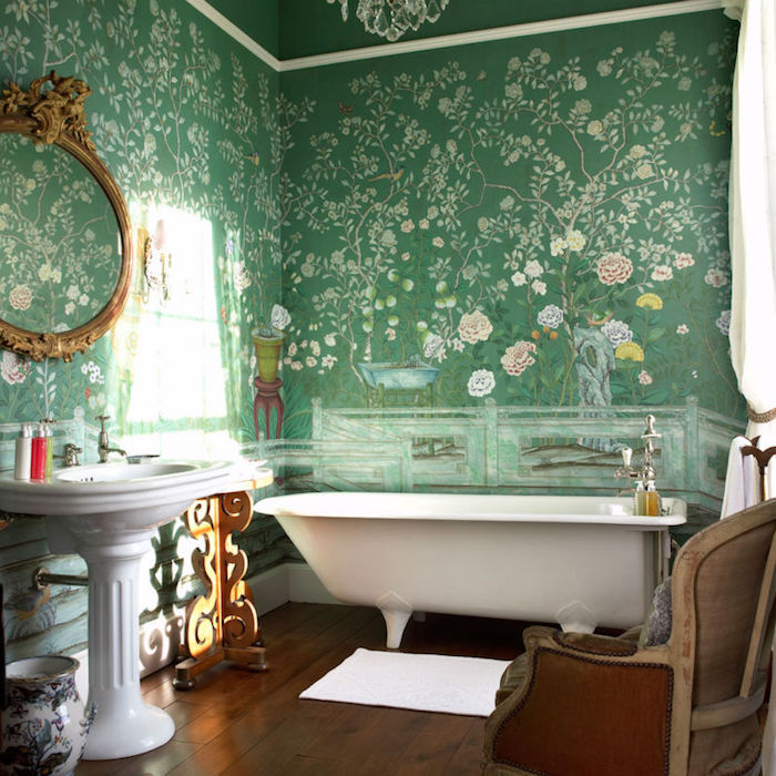 roses and trees, painted on the green walls of a bathroom, decorated in antique style, wooden floor and ornate sink, antique chair and a tub