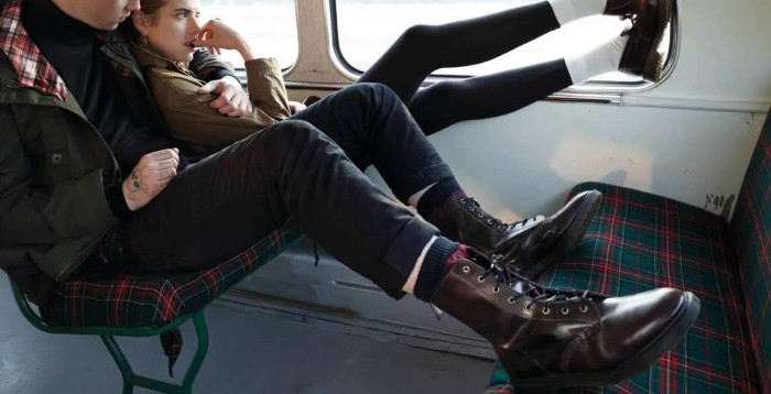 hugging young couple sitting in a bus, the boy is wearing skinny trousers, green parka and brown lace up combat boots, 90s outfit ideas, the girl is wearing black leggings, whites socks and a khaki jacket