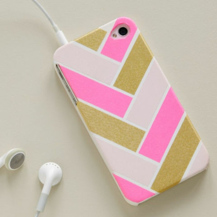 cute gift ideas, mobile phone case in white, decorated with hot pink, shimmering gold and pale pink strips, white earplugs attached to it