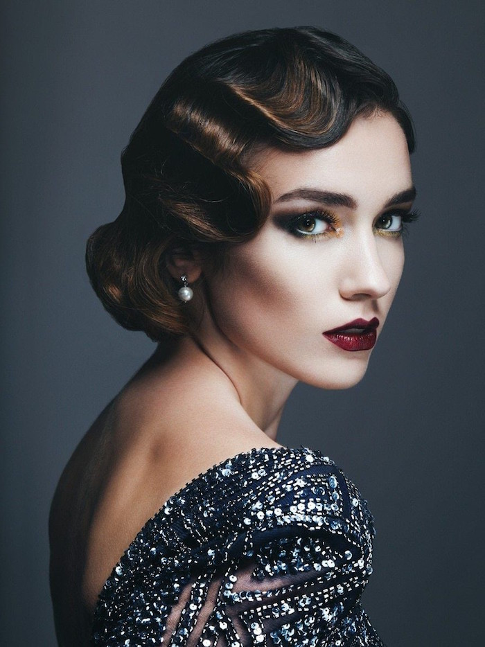 wavy bobbed brunette hair, worn by a woman with 1920s make up, dark eyeshadow and red lipstick, backless dress covered with silver sequins