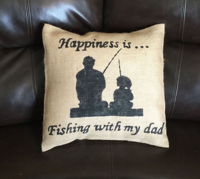 silhouettes of a man and a little girl, both holding fishing rods, decorating a pale beige cushion, with the inscription, happiness is...fishing with my dad