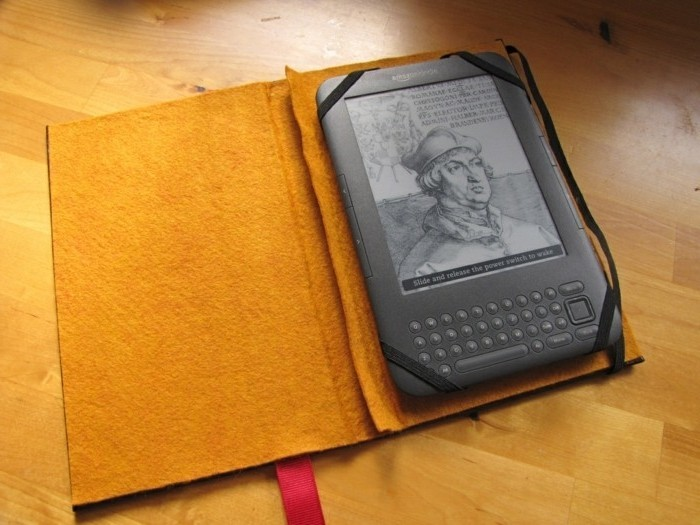 kindle inside a protector, shaped like a book, with hard beige covers, and a red bookmark, handmade gifts, placed on a laminate floor