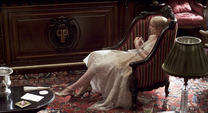 carey mulligan as daisy buchanan, wearing a light cream, embroidered silk dress, with a cream tulle side bow, and t-bar shoes, sitting in an antique armchair, great gatsby outfits