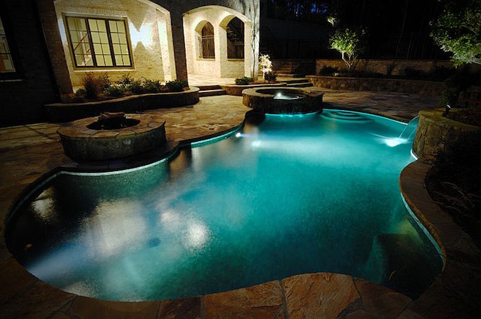 night photo of a pool, lit from within, near a fire pit, in the back yard of a house, with a lit porch light