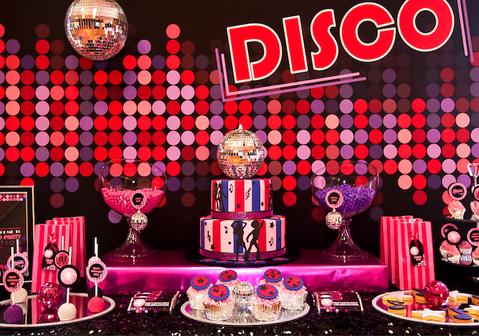 purple red and pink polka dots, on the wall near a party table, with a red white and blue striped cake, various different kinds of sweets, and two disco balls, 60th birthday party ideas, retro disco theme