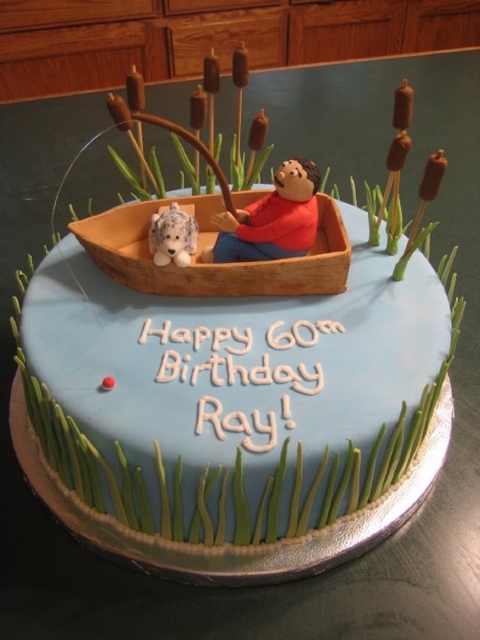 man with a fishing rod, and a small dog in a boat, decoration made from colourful fondant, on top of a pale blue cake, with grass and fondant reads, happy 60th birthday ray, written in white
