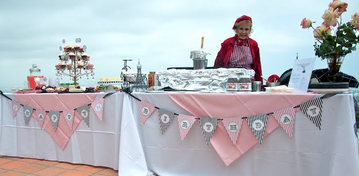 woman dressed in red, standing near two tables, with white and pale pink tablecloths, 60th birthday party ideas for mom, cupcakes and a crepe station