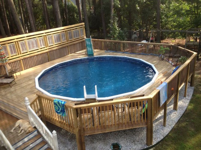 swing set and lots of tall trees, near a patio pool, with a tiny slide, small above ground pools, sleeping dog on the pool stairs