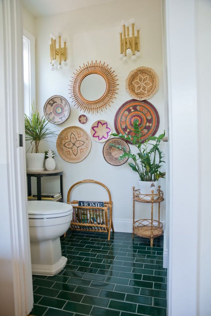 circular wall decorations, which ethnic patterns, on the wall of a room, with olive green, subway tiles on the floor, potted plants and a white ceramic toilet bowl, small bathroom décor