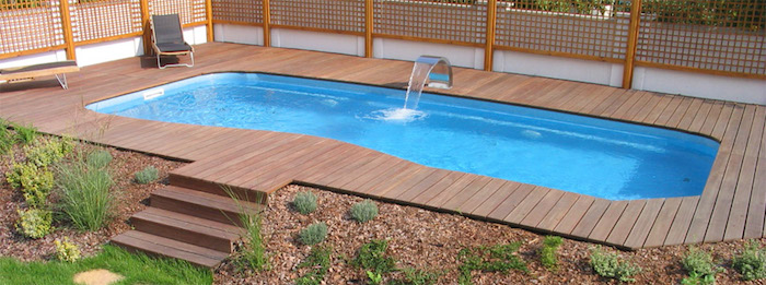 metal faucet pouring water, into a small rectangular pool, surrounded by wooden planks, pool patio ideas, with stairs