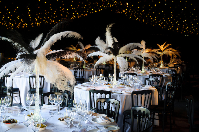 ostrich feather centerpieces, on several tables, set for a fancy dinner, with white tablecloths, and black chairs, 60th birthday party ideas, roaring 20s inspired setup