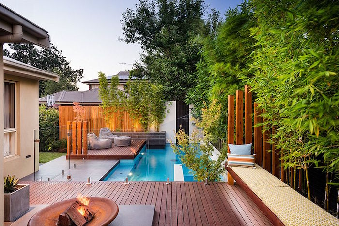 blue pool in a garden, with a patio, a fire pit, a sitting area, and various trees, small inground pools