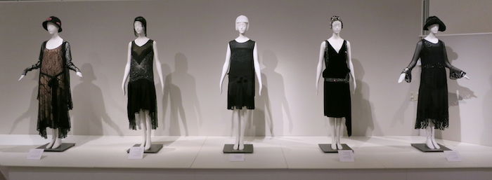 examples of roaring 20s dress, five gowns in brown and black, featuring low waists, fringe details and embroidery, worn by mannequins