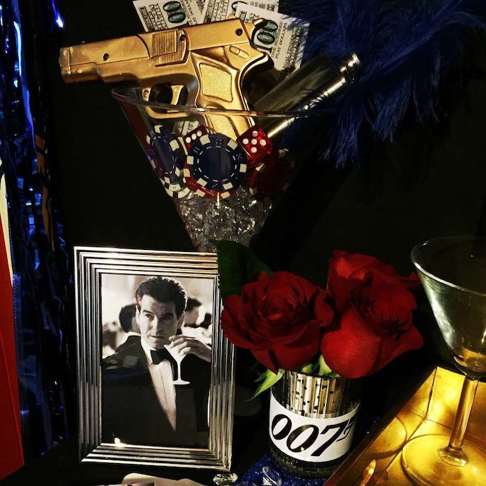 photo of piers brosnan, holding a martini glass, in a silver frame, next to a large decorative glass, containing a toy gun in gold, gambling chips and dices, and faux money, 60th birthday party ideas for men, 007 themed celebration