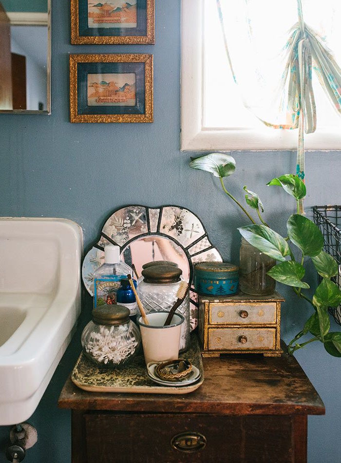 close up of diy bathroom decorations, in boho style, flower-shaped mirror and a potted plant, images in gold ornate frames, on a pale blue wall