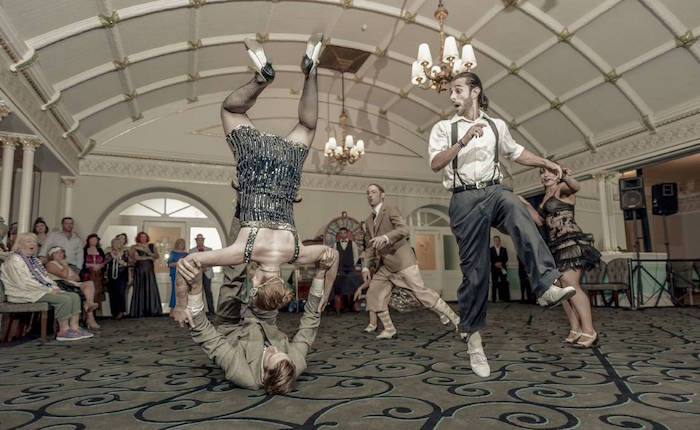 hall with a retro ornamental carpet, and a decorated ceiling, people dressed in roaring 20s fashion, dancing and flipping int he air