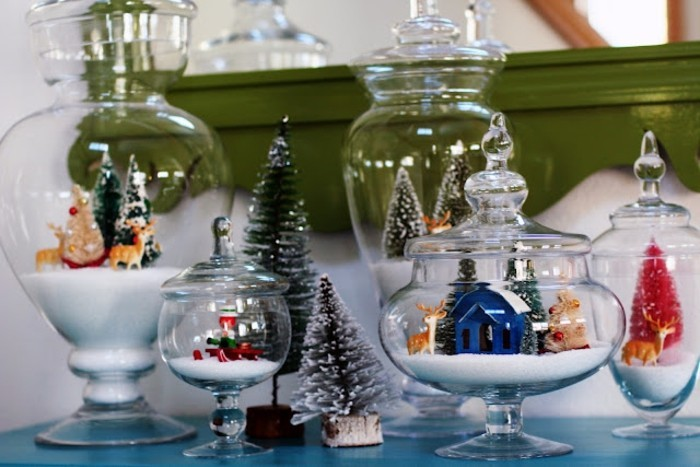 several clear glass containers, in different shapes and sizes, with ornate lids, each containing faux snow, and christmas-themed figurines, homemade gift ideas, tiny fir trees