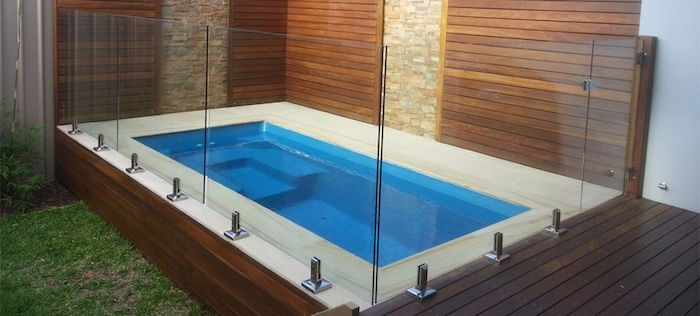 panels made from clear glass, surrounding a blue rectangular pool, built in the corner of a yard, backyards with pools, patio and lawn